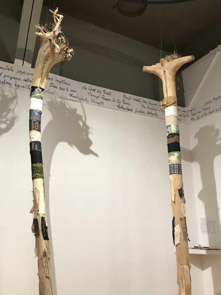 "Around The World: Unity in Diversity,  2017 - 2018 12 driftwood tree trunks, multi-cultural fabrics, paper ""barks"" Installation view at the Red Head Gallery   Mottos of Many Countries , 2018 Paper, ink, mottos from Wikipedia Installation view at the Red Head Gallery"