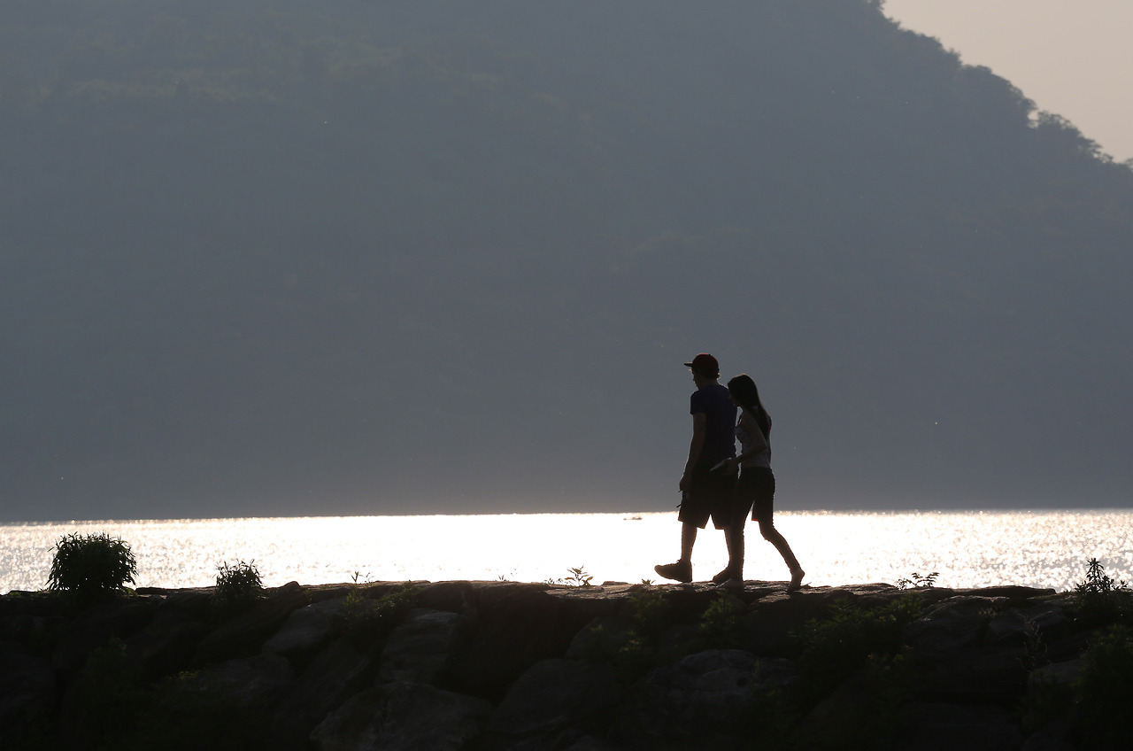 A couple walks on an outcropping of rocks at the Peekskill Waterfront, N.Y.