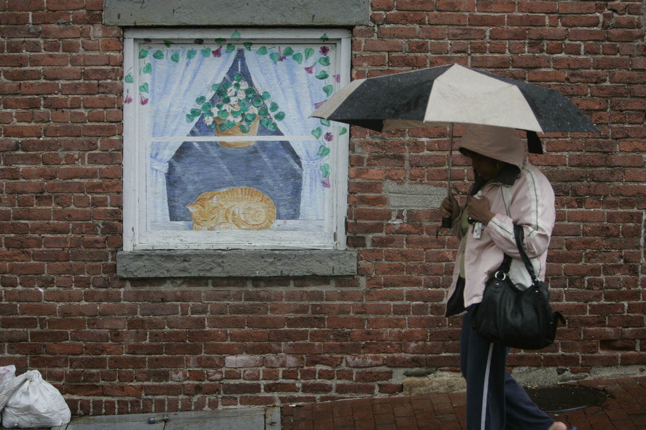A woman hurries past a mural in the rain in Peekskill June 13, 2013. (Dave Gershgorn/ The Journal News)