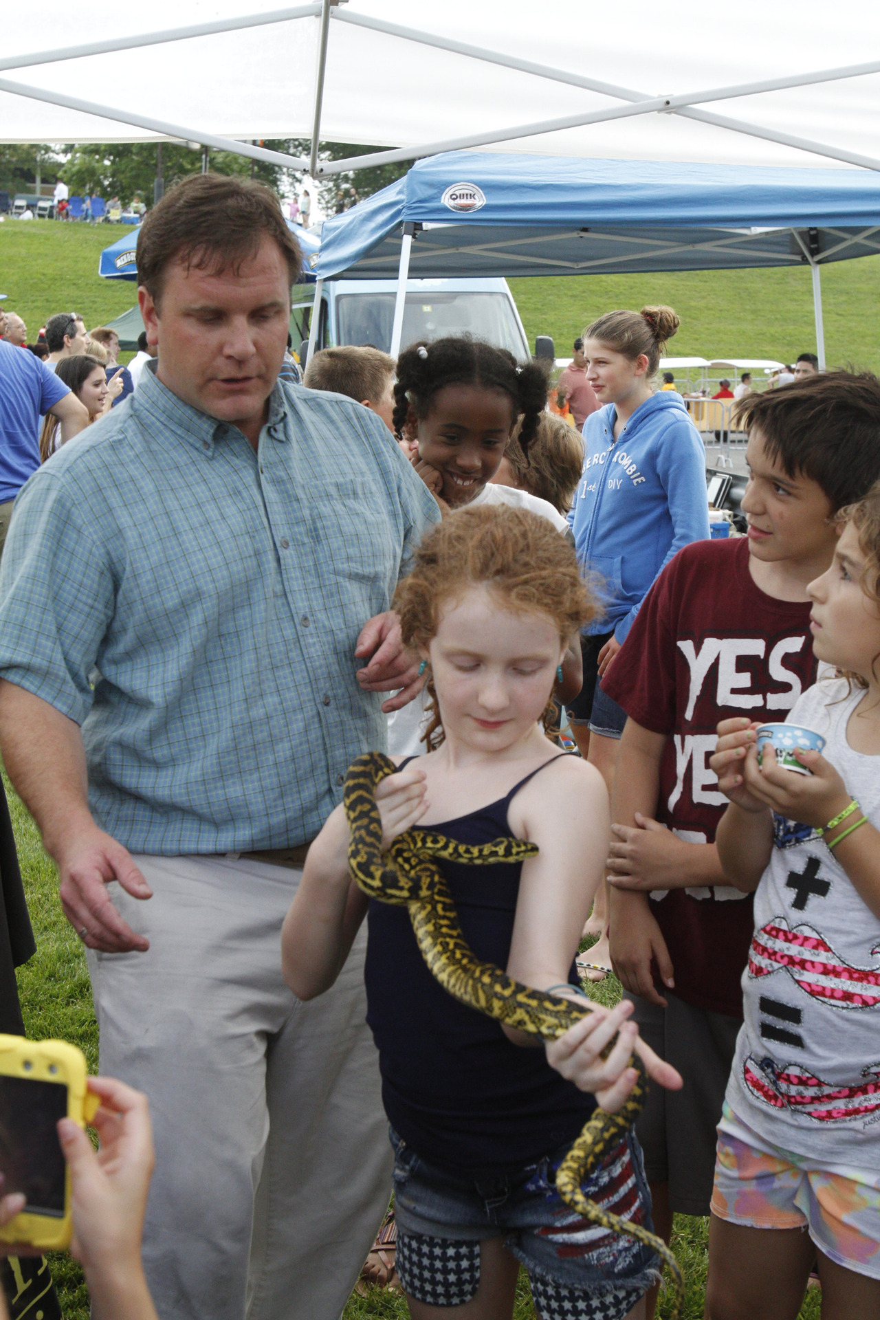 Celia Holden, 9, of White Plains holds a snake under the watchful eye of Chris Evers, founder of Animal Embassy based in Stamford, Conn. (Dave Gershgorn/ The Journal News)