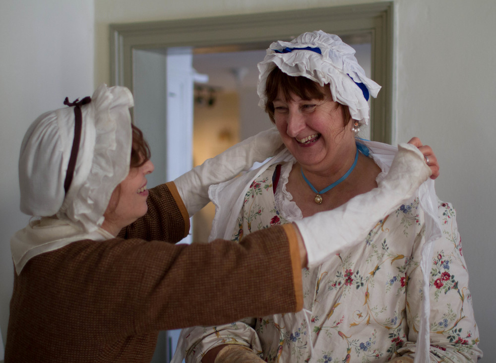 Christine Burgess, right, of Syracuse, is helped into her colonial attire by Kathy Wright, of Pelham, before a lecture on Thomas Davies at the Thomas Paine Cottage in New Rochelle Jan. 4. (Dave Gershgorn/ For The Journal News)
