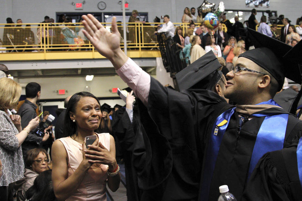 Graduate Jonathan Rivera, right, waves to his family while his sister Rosalina, left, watches him walk to Pace University's Westchester Undergraduate Commencement May 23, 2014. (Dave Gershgorn for The Journal News)