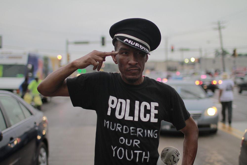 A protester walks the streets of Ferguson, Mo., imitating an officer's uniform. (Dave Gershgorn)