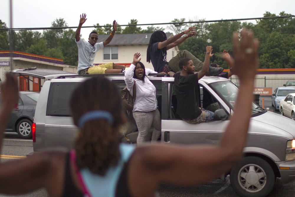 """Protesters took to vans and SUVs, riding up and down W Florissant Ave, honking and chanting """"Hands up, don't shoot."""" (Dave Gershgorn)"""