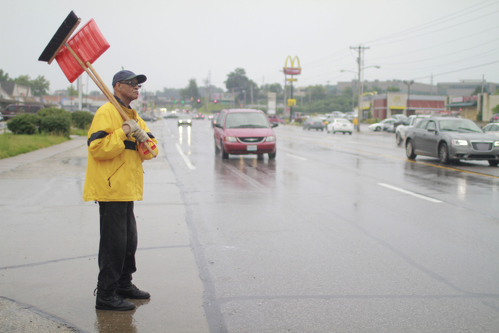 A volunteer waits to cross the road to help more businesses along W. Florissant Ave. in Ferguson. (Dave Gershgorn)