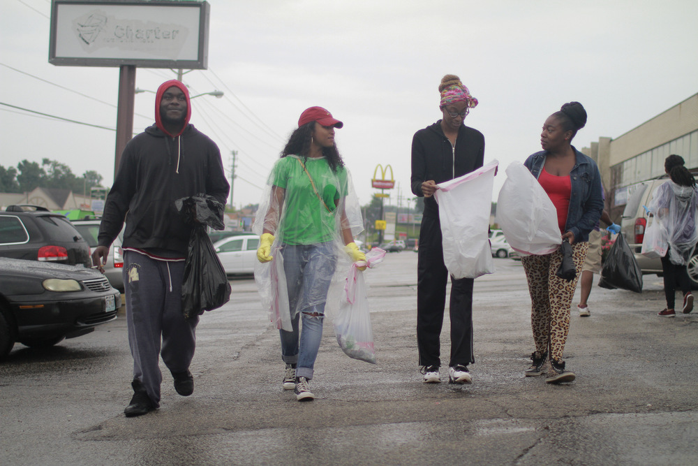 A group of young people walk from business to business, helping clean up debris from Friday night's looting. (Dave Gershgorn)