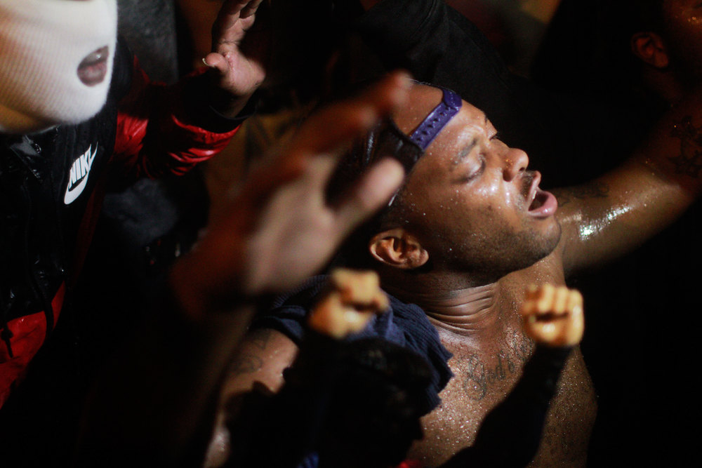 A protestor of Ferguson's curfew puts his hands up in a show of support for Michael Brown, an 18-year-old killed by police officer Darren Wilson.
