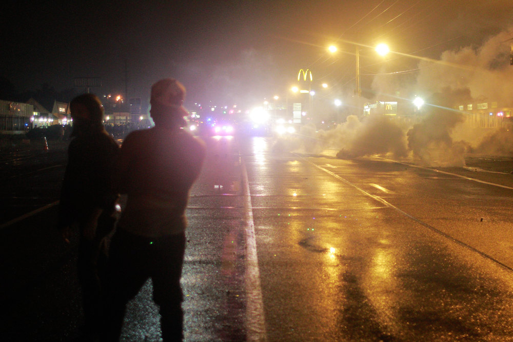 Police fired volleys of smoke and tear gas into the crowd of protesters, dispersing a majority of those defying Ferguson's curfew. (Dave Gershgorn)