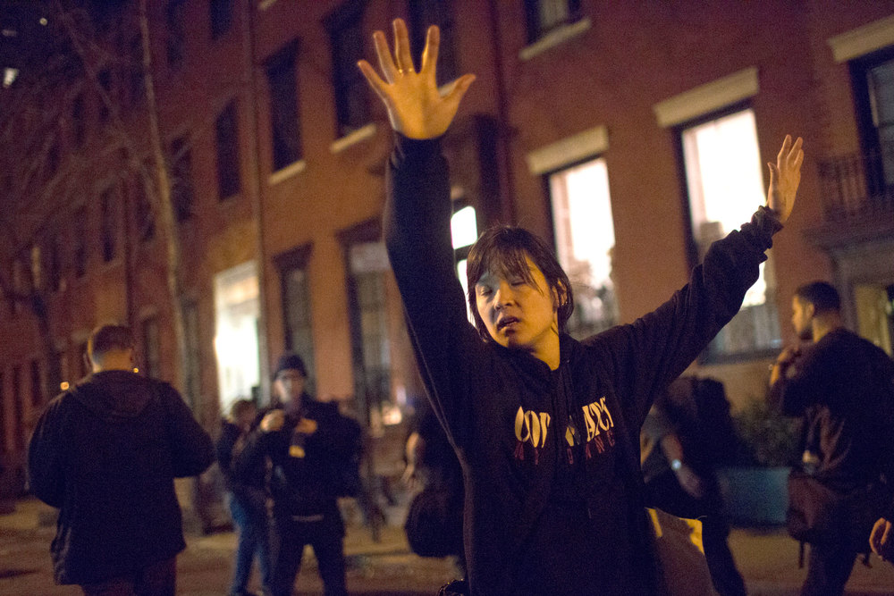 A protestor raises her hands during a NYC Ferguson protest.