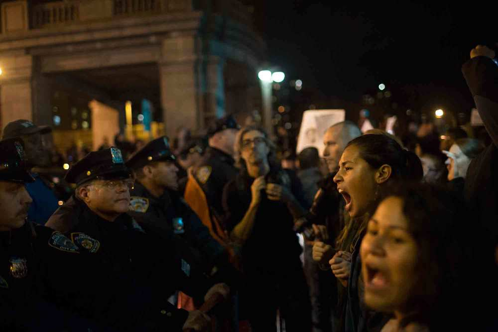 Protestors briefly clashed with police officers at the entrance to the Williamsburg Bridge Tuesday night, only to be repelled and pass over the Manhattan Bridge.