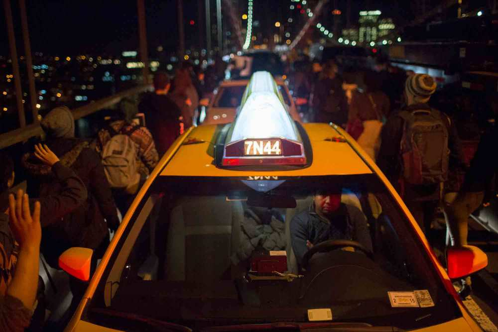 A taxi driver waits on the Manhattan Bridge Tuesday, as hundreds of protestors filter through the stationary cars.