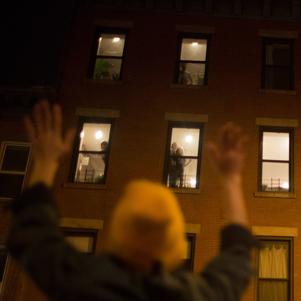 Brooklyn residents watch out their windows Tuesday as protestors pass by their apartment building in Prospect Heights.