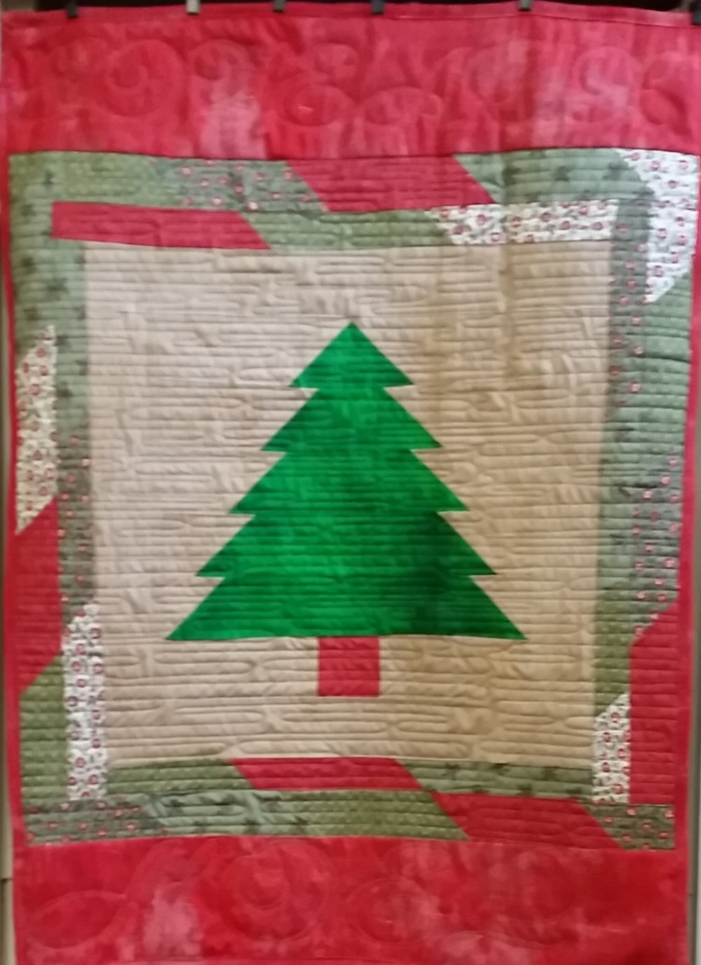 "We made a small hanging using a 12"" block and some strips and scraps of Christmas fabric."