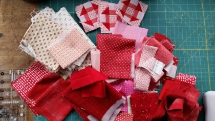 "For Valentine's I am starting with a pile of pinks, reds and some lights for background in my blocks. Look at all that delicious Moda Fabric! This mini would be charming made up in brights, low volume, civil war, ....almost any fabric that makes your quilter's heart happy♥  You'll need to make some Half Square Triangles (HSTs) for your mini Churn Dash blocks.  In this tutorial I will showcase using the Creative Grids 4 in 1 Half Square Triangle Ruler CGRBH1 to make my HSTs......But you can create your your HST using any method you like for your little quilt.  As long as they will finish to 1"" x 1"" size ."