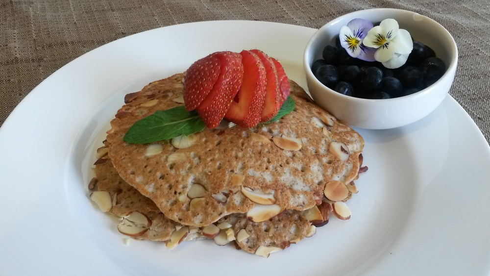 Pancakes made with ground oats, ground chia seeds, almond flour, almond milk, coconut oil, and almond slivers.