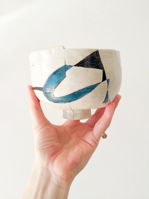 Pinch pot with a foot and abstract design. White stoneware clay with underglaze.