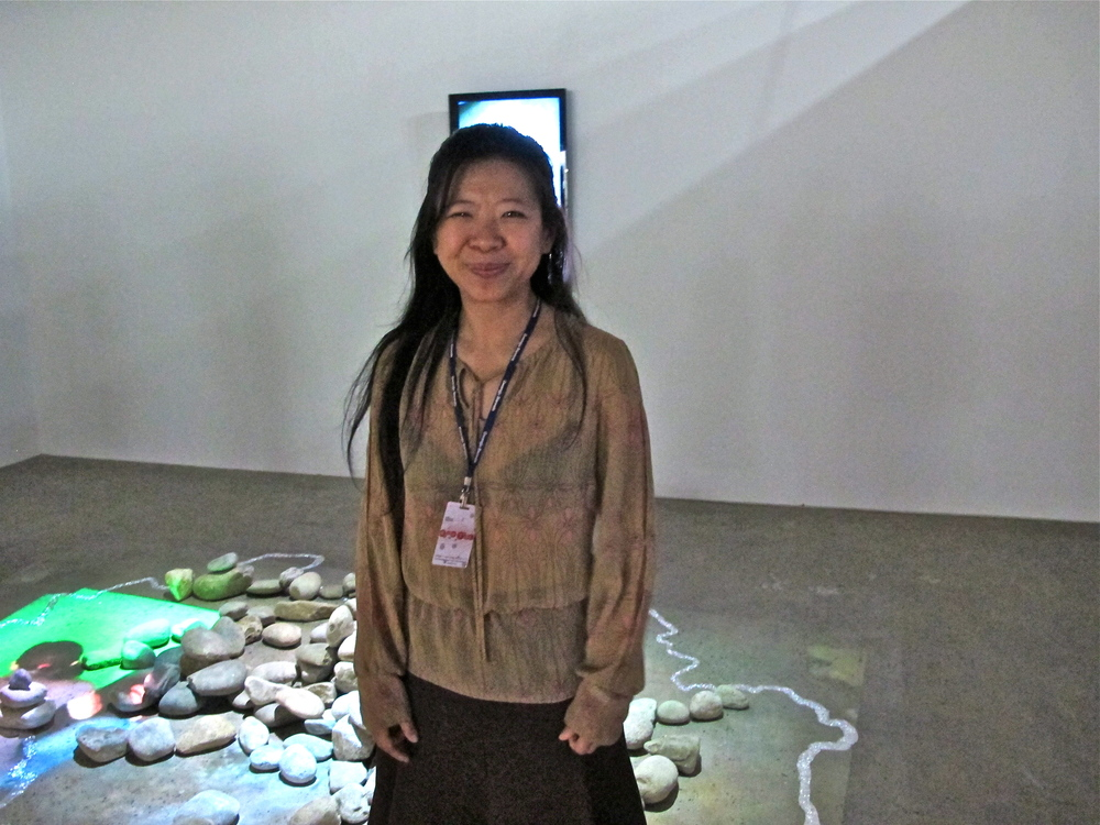 Indonesian artist Tintin Wulia in front of her installation,  Nous ne otons pas le fleurs , 2012