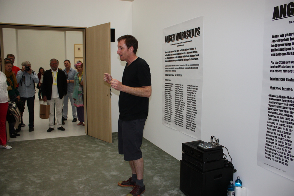 Stuart Ringholt,  Anger Workshops.  Neue Galerie. During the workshops visitors are offered the opportunity to express their anger using voice and movement to the sound of loud house music for five minutes before then embracing other members of the group. The room is closed to the public, although the sound of the workshops can be heard outside its walls. © Lucy Rees