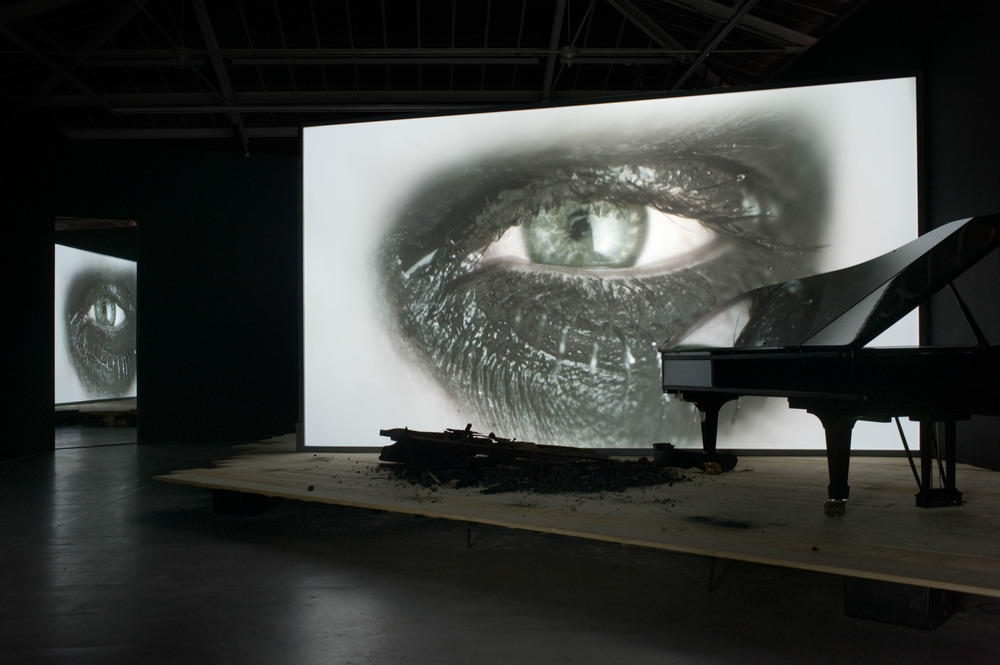 Douglas Gordon , Phantom, 2011  stage, screen, a black Steinway piano, a burned Steinway piano, one monitor, dimensions variable. Courtesy Studio lost but found and Galerie Yvon Lambert, Paris.  Rufus Wainwright, ALL DAYS ARE NIGHTS: SONGS FOR LULU used courtesy Decca Label Group. Photograph: Studio lost but found and Katharina Kiebacker, VG Bild-Kunst Bonn