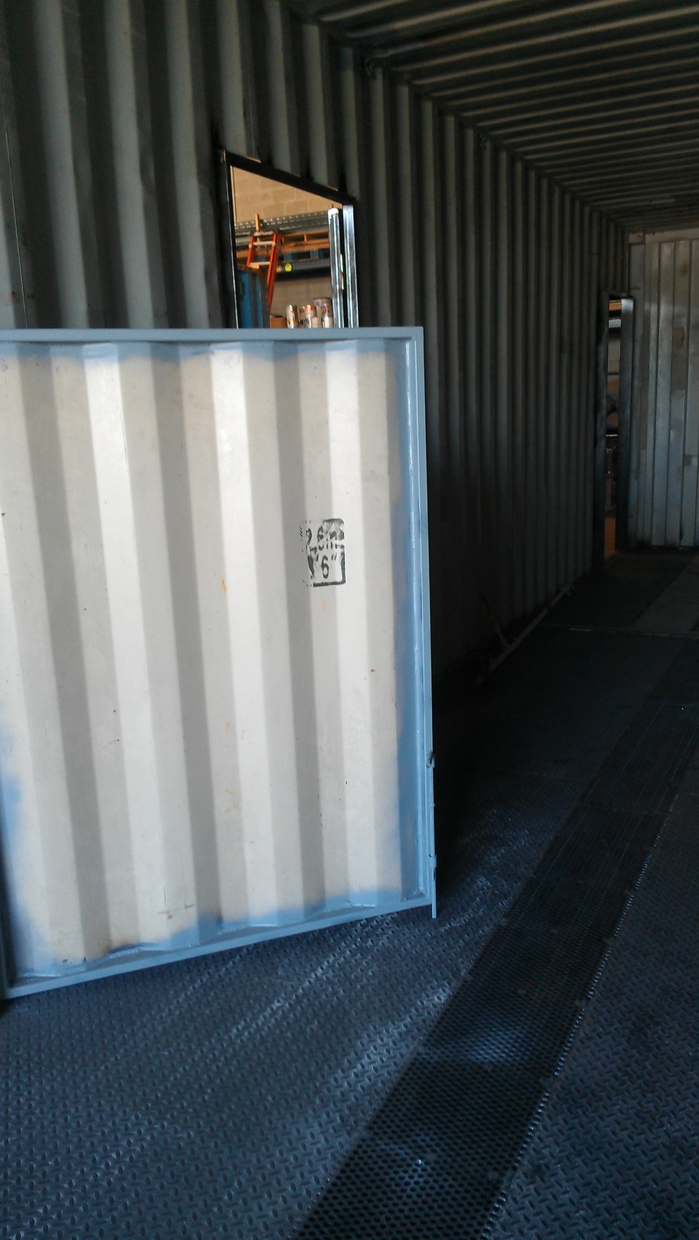 Fire training container with swinging partition  hooks into place on diamond plate and grated floor