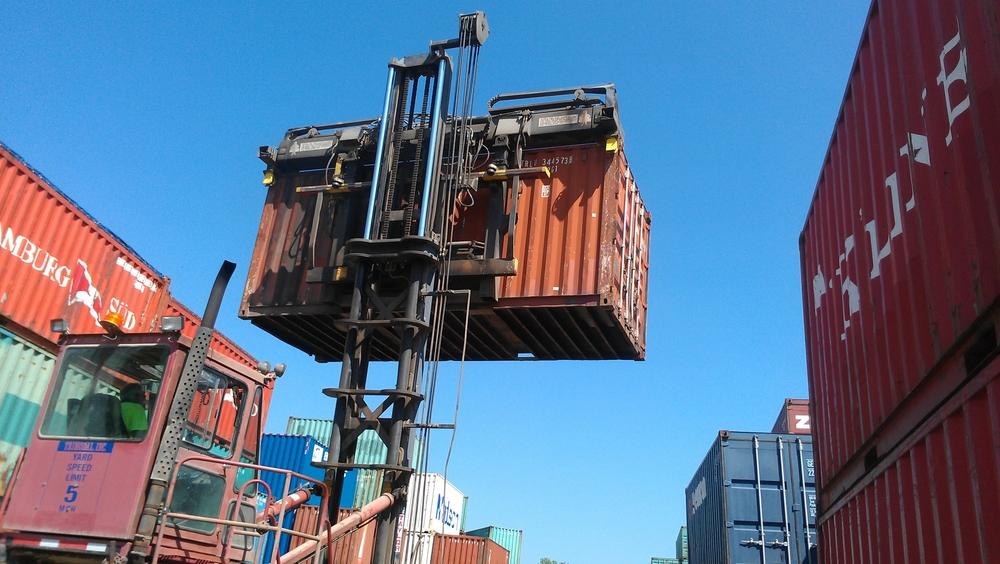 Container forklift picks up the container from the top 2 corners