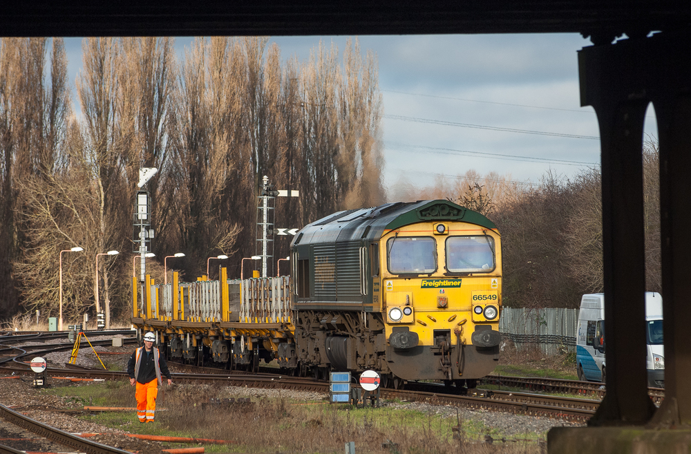 Freightliner 66549 leads a southbound engineering train past a survey crew working on the re-signalling project that will doom Banbury's signal boxes and semaphores.