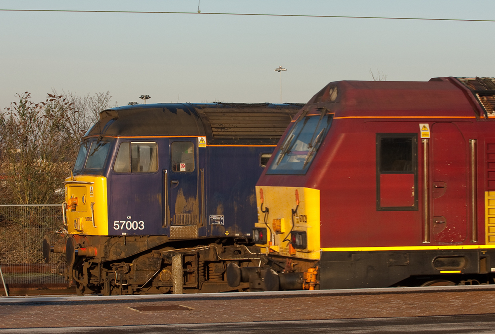 A study in styling, EWS 67021, a Spanish-built, EMD-design JT42HW-HS, drifts past DRS 57003, an EMD re-engined, British-built Brush Type 4, a product of the Brush Falcon Works in Loughborough.