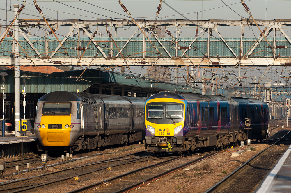 Departing for Manchester Airport, TransPennine Express Desiro No. 185118 passes an East Coast HST stopped at Platform 4.