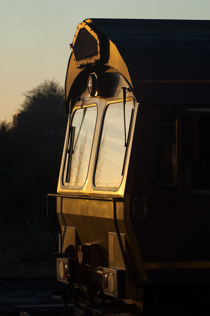 Setting sun highlights the distinctive profile of EWS Class 66 No. 66143, waiting for a signal to head north from Peterborough with a WBB minerals train.