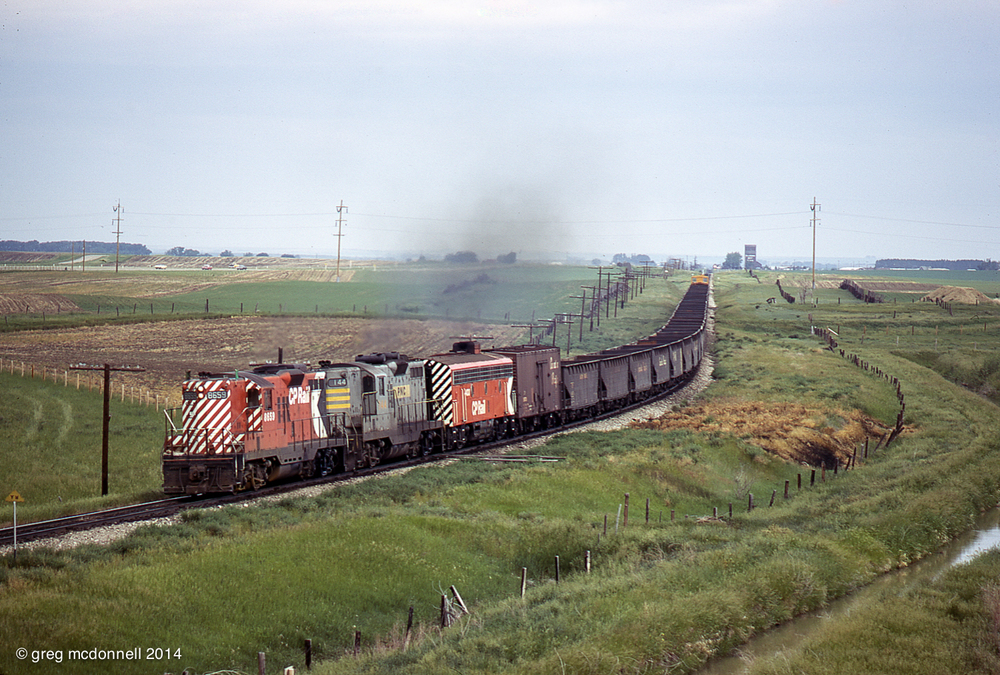 Flying green, First 70 departs Coalhurst with CP 8659, PNC 144 and CP 4433 hauling ballast hoppers. The headlights of two following east bounds are visible alongside the Alberta Pool elevator on the horizon.