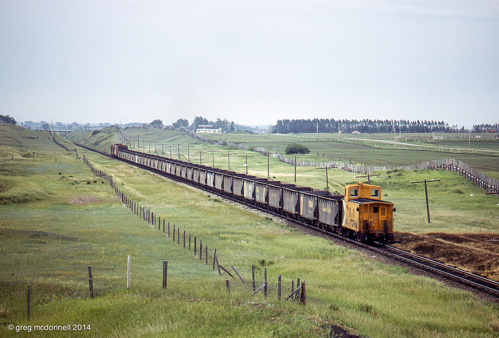 An Angus-built steel van brings up the markers as First 70 rattles eastward from Coalhurst, Alberta, June 20, 1974.