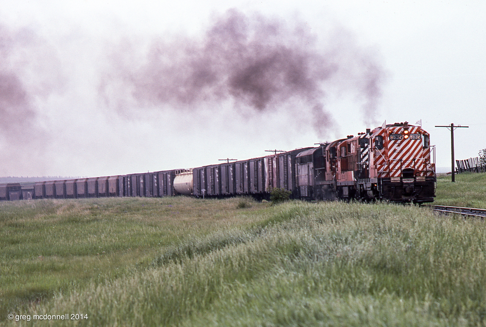 Extra 8632 West slipping wildly on the approach to Cowley, Alberta, on June 20, 1974. Three-builder lash-up includes far-from-home RS18 8760 bracketed by FMs 8555 and 4065. The sound was incredible, but the best was yet to come.