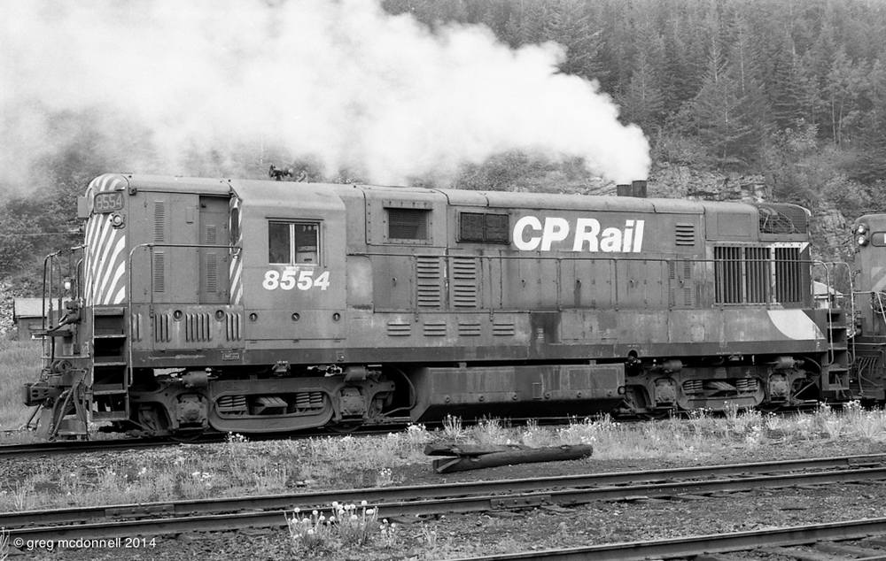 Nothing like the smell of opposed-piston exhaust in the morning; CP 8554 on the shop track at Crowsnest, B.C. June 21, 1974