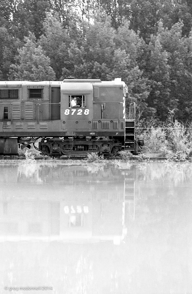 CP 8728 casts its reflection in the floodwaters as the hogger keeps a close eye on track conditions.