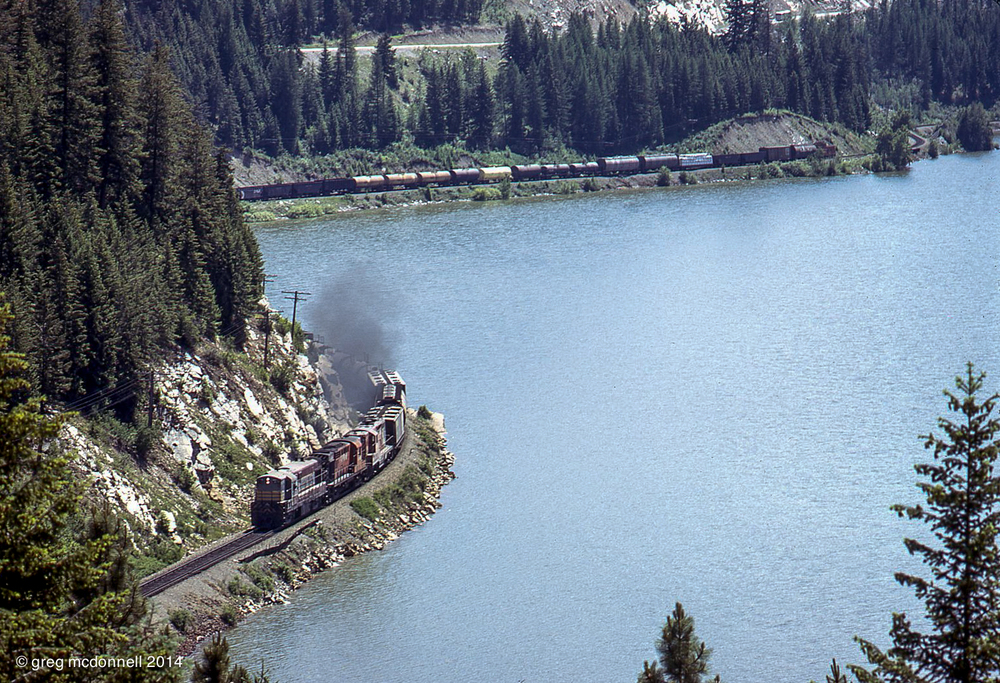 Tracing the shore of Moyie Lake, No. 980 approaches Jerome Tunnel. Matching the CLC up front, a script-painted van brings up the rear of the eastbound manifest.
