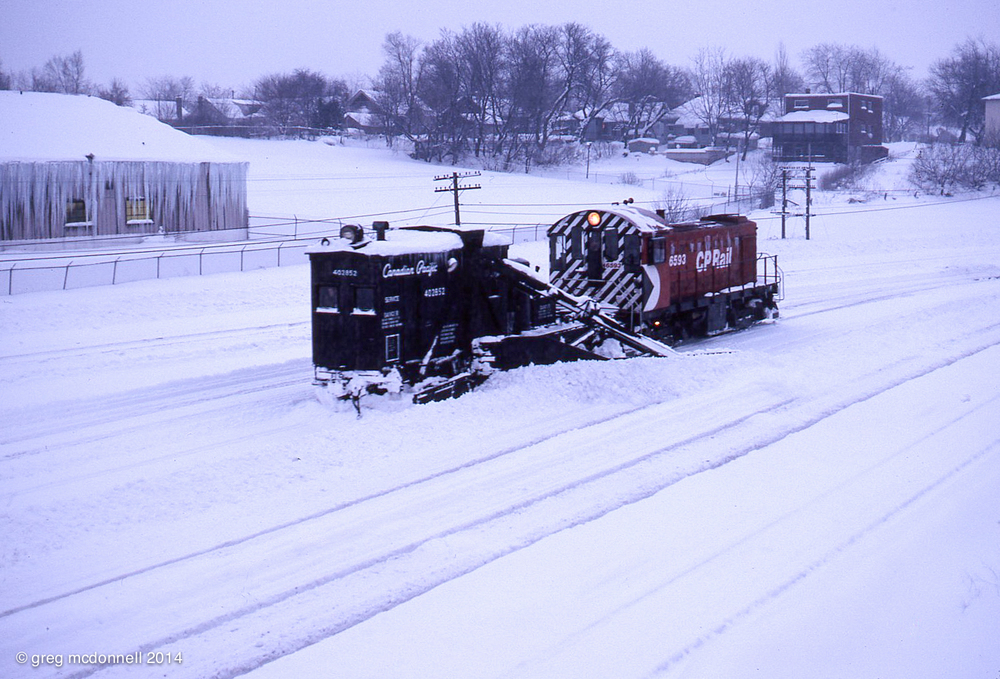 Six hundred and sixty horsepower never sounded so good. Plowing the yard at Quebec Street in London, Ontario, CP 6593 shoves a vintage spreader through axle-deep snow on December 12, 1977.