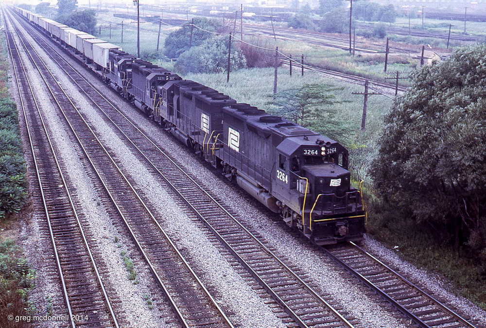 Viewed from the Tifft Street bridge, a quartet of Penn Central GP40s accelerate a westbound Flexi-van train out of town. The first three units, PC 3264, 3266 and 3271 were turned out of La Grange as solid-black EMD loaners numbered 15, 17 and 23. Trailing unit 3003 is a New York Central original.