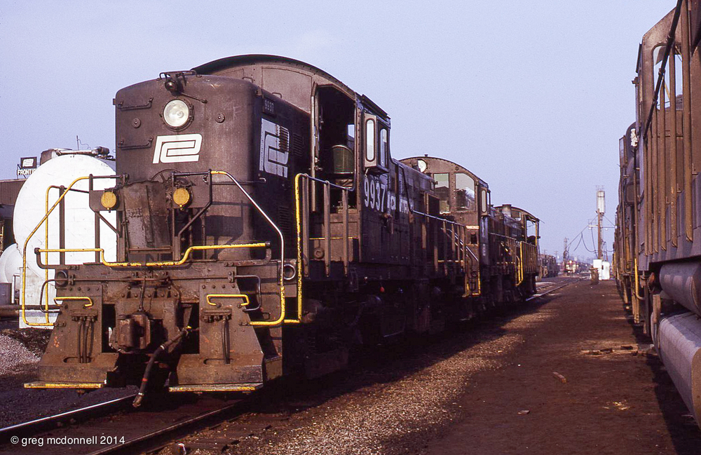Buffalo was a McIntosh & Seymour stronghold from the days of dieselization through the early Conrail years. Longtime Buffalo residents, ex-Pennsy RS1 9937, an S1 and an S4 take a break at Frontier. In the background, a trio of TH&B Geeps prepare for their overnight run to Toronto on PC/TH&B/CP run-through FT-1.