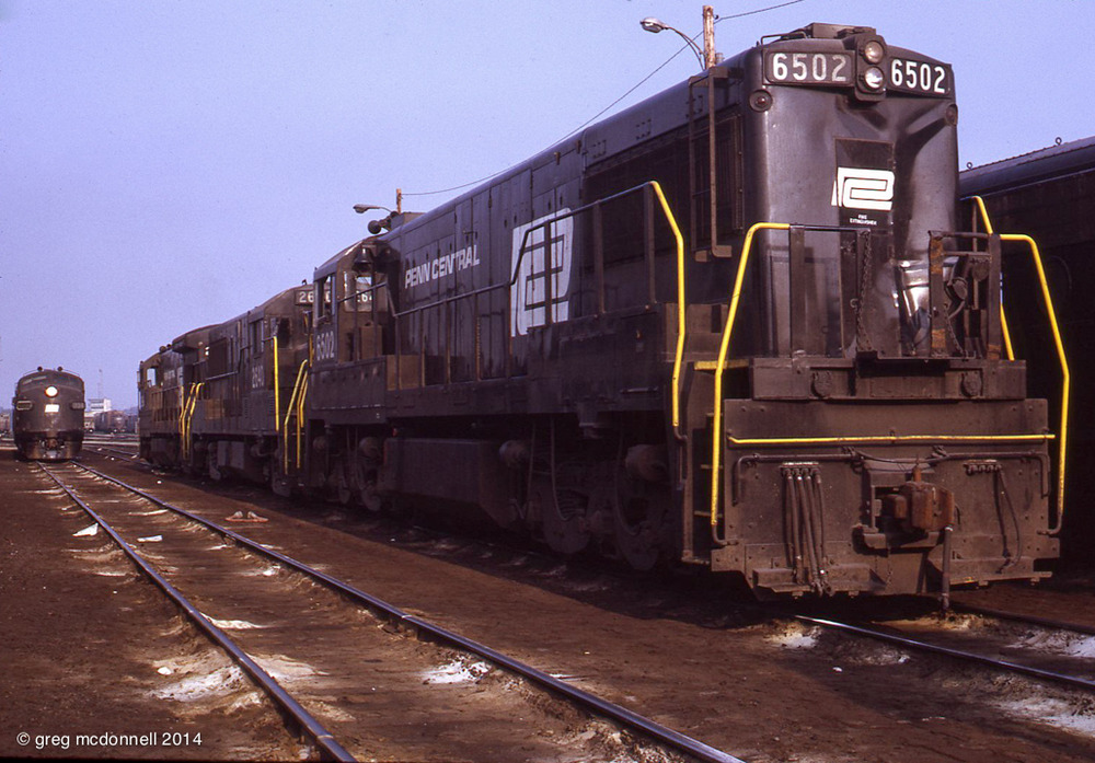 Still in fresh PC paint, former Pennsy U25C 6502, nosed onto a U25B and U33B, has taken a hit.