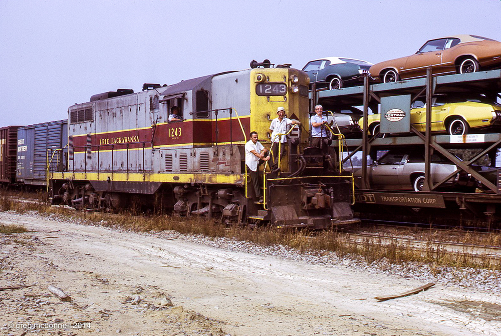 A full crew and nothing but smiles for the photographers as GP7 1243 races past a load of new Oldsmobiles at Bison. That's just the way it was in Buffalo.