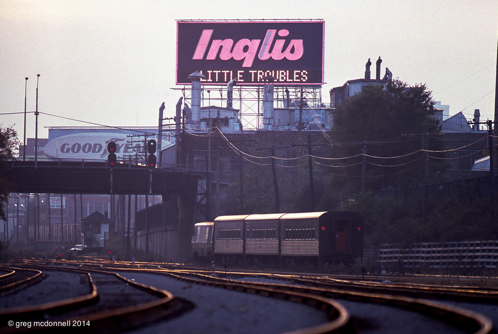 Au revoir. VIA No. 85, with LRC 6907 and three Tempo cars, slips past the Inglis sign at dusk on October 18, 1984. Cabin E, one of the least noted of the downtown Toronto towers is visible just beyond the Strachan Avenue overpass.