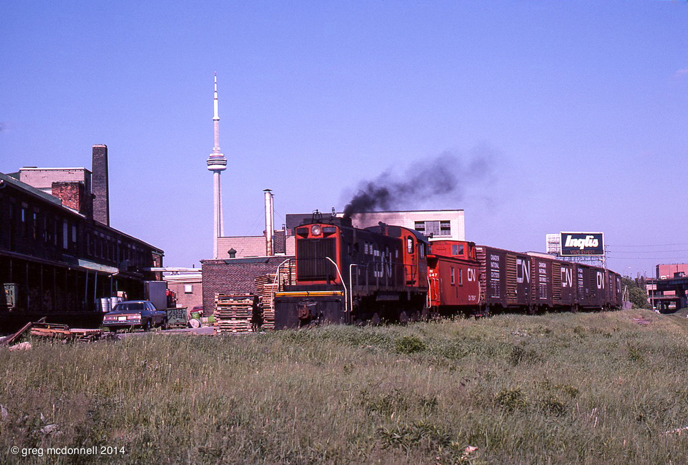 Switching in the back yard at Inglis on June 5, 1978, CN S13 No. 8520, a wooden van and a string of 40-foot boxes are flanked by icons of the Toronto skyline.