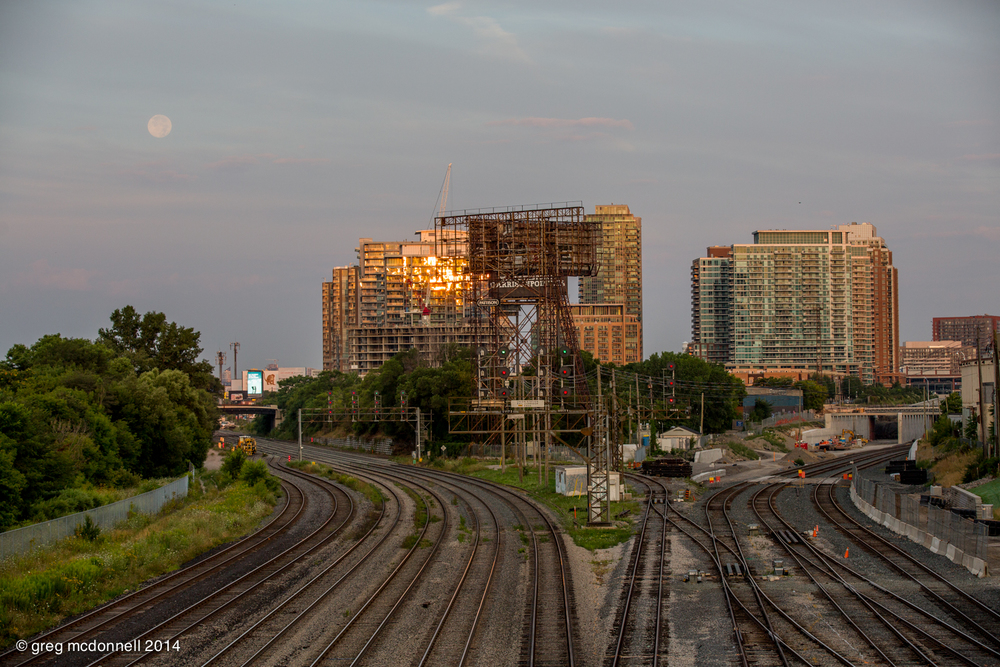 Moonset and condos reaching for the sky. Progress, in the form of new trackage and grade separation for the long-overdue airport link, continues to alter the scene.