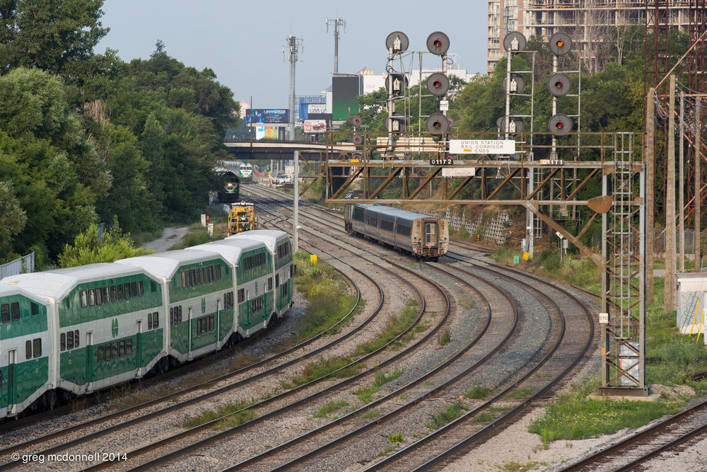 Chasing an outbound GO train, VIA No. 71 sprints for Windsor as an eastbound lakeshore train approaches and an equipment move holds for traffic.