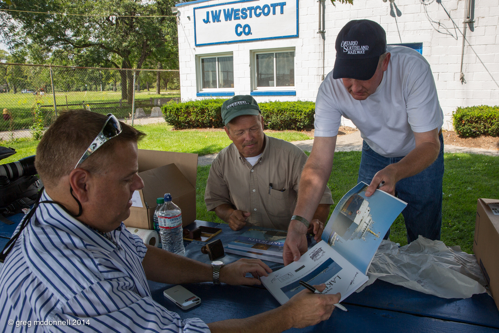 Upholding tradition, Mike, Jeff and Brad sign the first copy of Lake Boats second edition at the J.W. Westcott Co. dock.