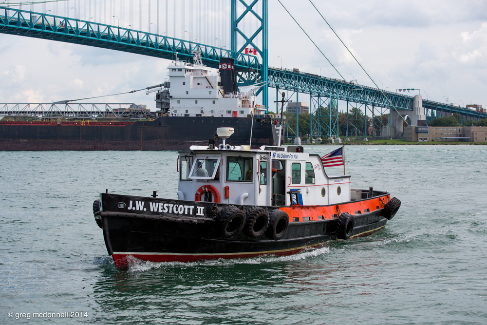 J.W.. Westcott II  returns home as Algoma Enterprise ducks beneath the Ambassador Bridge.