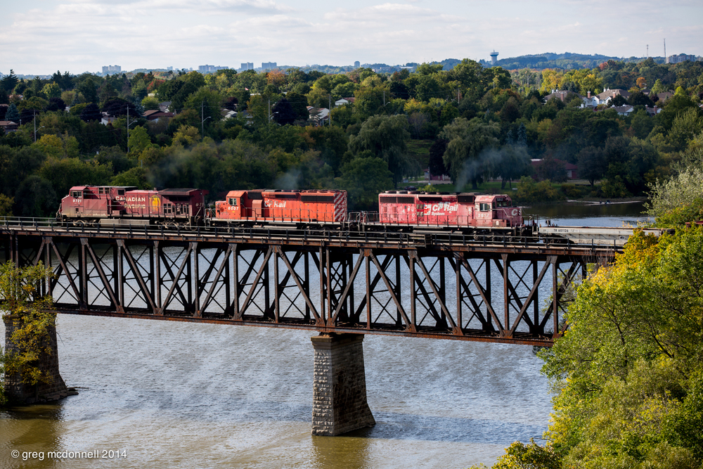 Worse for wear, but still earning her keep after more than 42 years, CP 5612 trails sister 6007 and AC4400CW over the Grand River bridge at Galt, Ontario, September 22, 2014.