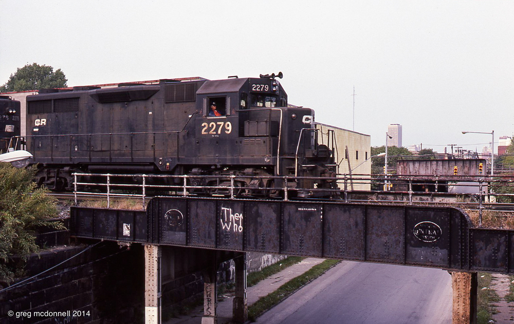 "I found the train stopped on the Howard Street overpass, with Penn Central-black GP35s 2279 and 2278 cooling their wheels after a gruelling few miles. ""The Who"" graffiti is nearly as nostalgic as the faded New York Central ovals."