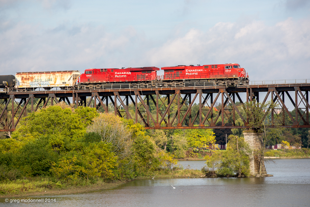 Crossing the Grand River bridge at Galt, Ontario, the engineer on an eastbound ethanol train checks out an evert and great blue heron fishing just off the island. October 7, 2014.