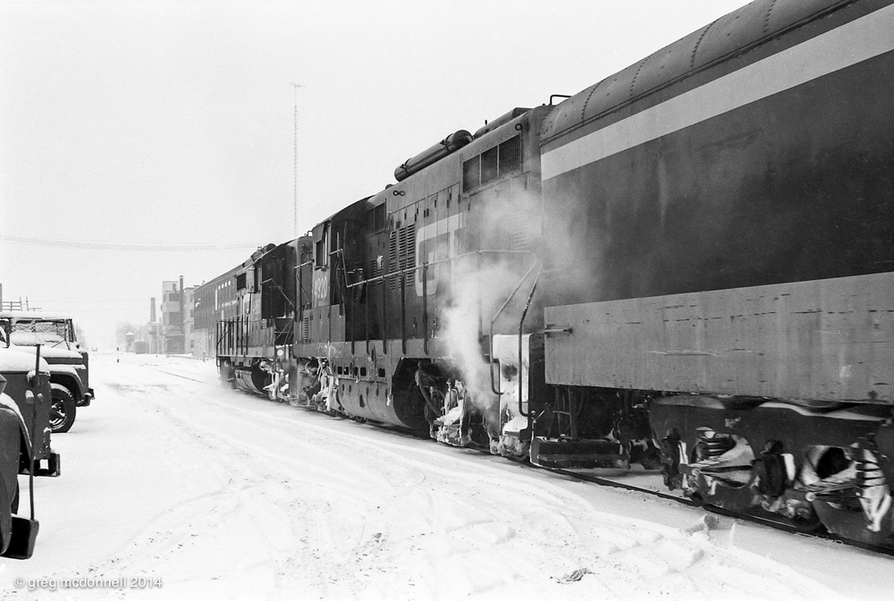 Chicago-bound, GTW 4950 and 4920 accelerate westward, framed between the snow-covered CN Express trucks parked at the sheds and the row of factories that stretch to the King Street crossing.